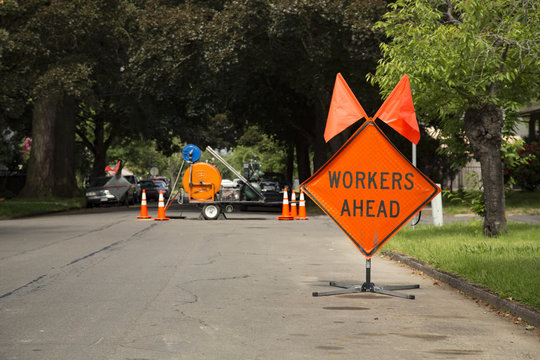 """Orange and Black """"Workers Ahead"""" Sign in Residential Neighborhood with Equipment in Background, Daytime"""