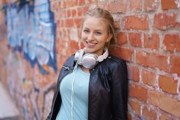 selbstbewusste junge frau lehnt an einer wand mit graffiti und lächelt