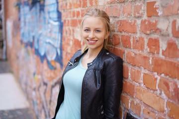 junge frau lehnt entspannt an einer wand mit graffiti