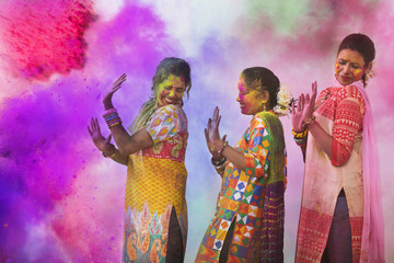 Three Young Indian Women With Colored Face Dancing During Holi Color festival