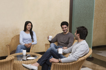 Happy young friends having coffee together while sitting on wicker chair at home