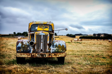 Old pickup standing on a harvested field