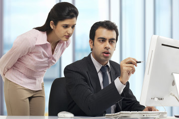 Businessman showing something to a female executive