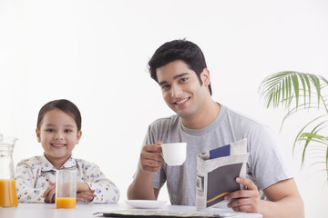 Portrait of young father with his daughter having breakfast