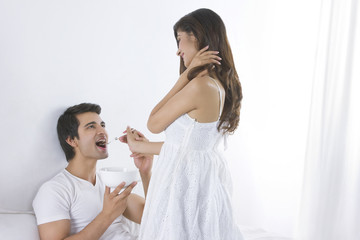 Happy young woman feeding man in bedroom