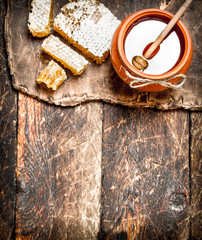 Wall Mural - Honey pot and honeycomb with a wooden spoon.