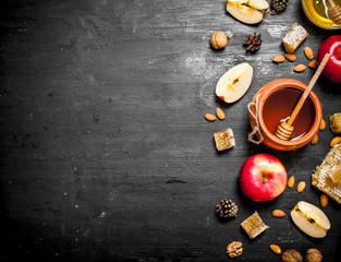 Honey background. Honey in pot with slices of ripe apples and nuts.