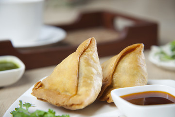 Close-up of samosas with sauce in plate