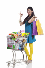 Portrait of a woman with a shopping cart and shopping bags giving ok sign
