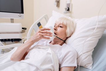 Delicate sore woman taking off her oxygen mask
