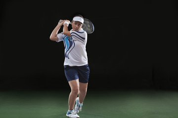 Young female player playing tennis over black background