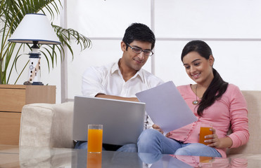 Young couple sitting on sofa using laptop while reading document