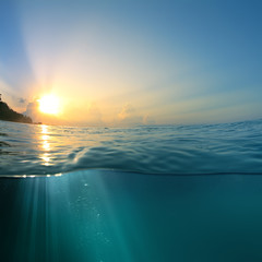 Beautiful sky with the sun image splitted by waterline. Air bubbles and sunrays underwater
