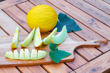 Melon, yellow on colorful wood background