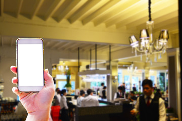Hand holding smartphone on the restaurant background