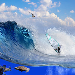Separated image with waterline. Oceanview with breaking surfing wave and professional windsurfer on a board under sail and sealife with fish and tortoise swimming over coral reef