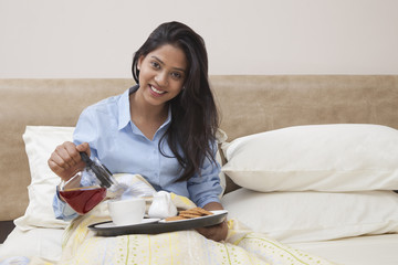 Portrait of beautiful young woman pouring tea in cup while sitting in bed