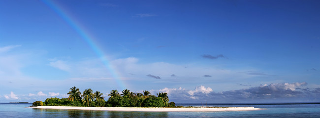 Merged Panoramic image. Tropical maldivian island in daylight with rainbow on horizon and white sandy beach