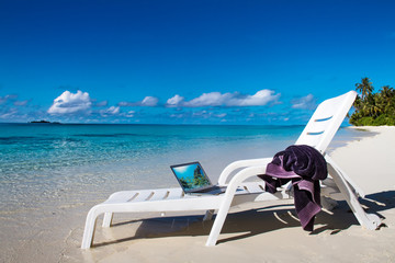 Travel vacation story of tropical beach with mobile computer and towel on chair. Beach laptop as mobile office. Tropical seascape with notebook