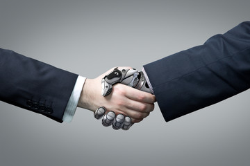 Businessman holding robotic arm in handshake