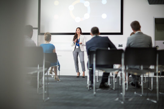 Businesswoman giving training to colleagues in conference room