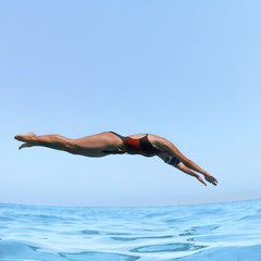 professional female swimmer jumping in blue sea water