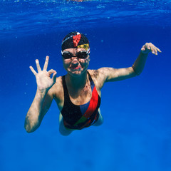professional female sport master smiling underwater and showing ok sign