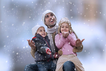 Father sitting with kids as it snows