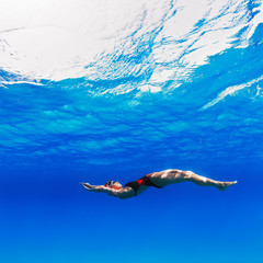 professional female swimmer moving on her back underwater in blue