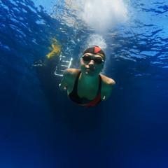 professional sport swimmer in dark swimglasses floating forward underwater in blue