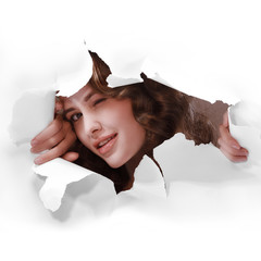 young girl smiling winking with one eye tearing white paper wall breakthrough design element template