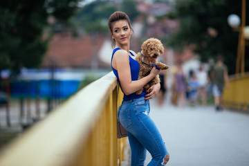 Portrait of beautiful young woman with her little red poodle puppy.