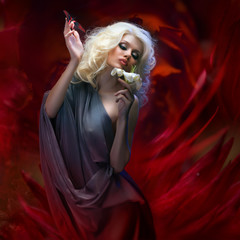studio portrait of beautiful blonde in gray cloth holding flower and tropical butterfly sitting on her hand on dark red abstract background
