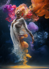 Fashion creative portrait of a blonde girl standing in clouds of watercolor paint