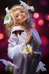 studio portrait of beautiful blonde with blue eyes wearing flowers in her hair and tropical butterfly sitting on her shoulder on shining abstract background