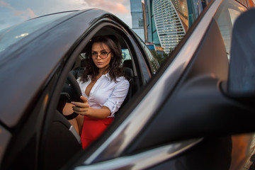 Business woman wearing red skirt sitting in a luxury car after work at evening