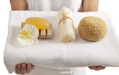 Woman holding a towel with bath products