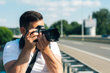 Young man with professional camera photographing outside.