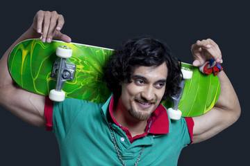 Close-up of young smiling man holding skateboard behind head against black background