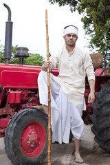 Portrait of farmer with stick and leg on tractor wheel