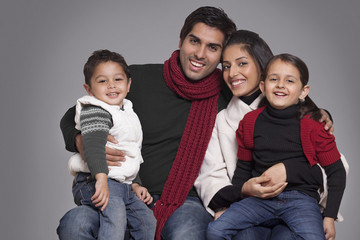 Portrait of smiling family over grey background