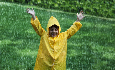 Cheerful boy wearing raincoat enjoying in rain