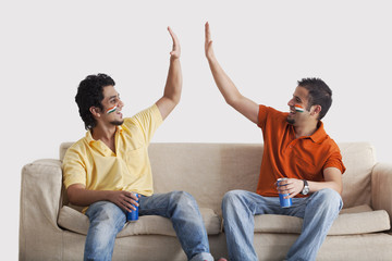 Happy young male friends in casuals giving a high-five to each other while holding tin cans