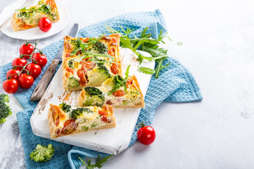 Delicious vegetarian homemade pie, Quiche with cherry tomatoes, broccoli and herbal cheese on old white cutting board. Healthy food concept. Copy space.
