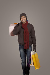 Portrait of young man carrying shopping bags