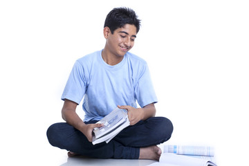 Smiling teenage boy with books against white background