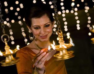 Woman lighting diyas