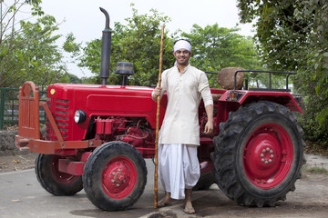 Portrait of a farmer with a stick standing next to tractor