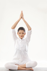Smiling young woman doing yoga over white background