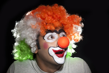 Surprise male clown over black background